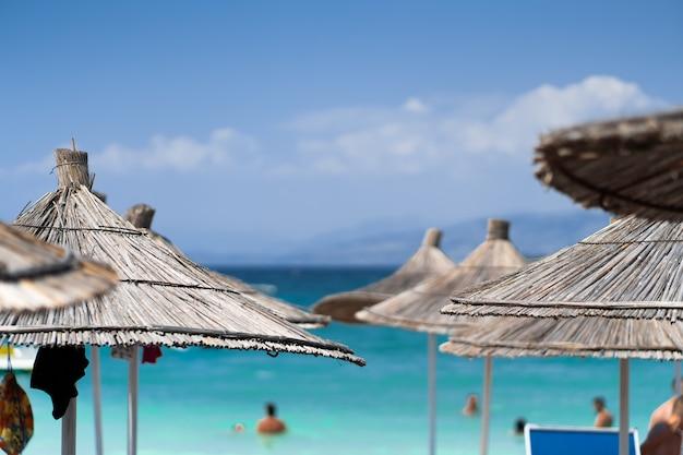 Стулья и зонтик в палм-бич тропический праздник баннер. пляж, пальмы и небо. летние каникулы путешествия праздник фон концепции. тропические пейзажи. горы. открытка
