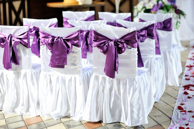 The chairs are decorated with purple bows