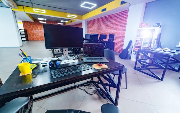 Стулья за деревянным современным столом с ноутбуками. широкое окно и желтый упор над ним. яркие наклейки на синей стене. концепция интерьера офиса.