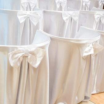 Chairs covered with white cloth on wedding ceremony in rows