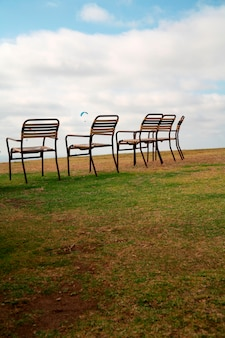 Chairs in field while parachute flying in sky