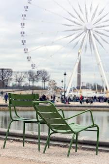 パリのコンコルド広場にあるグレートホイールの背景にある休憩用の椅子。フランス