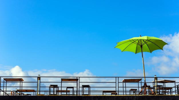 Chairs, table and umbrella on the balcony in blue sky