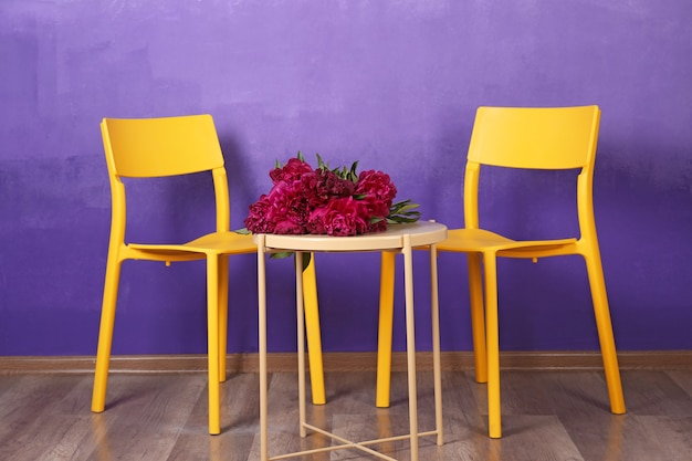 Chairs and table with peony flowers near lilac wall