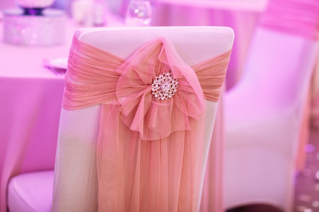 The chairs with bows and jewerly in the resturant on wedding day