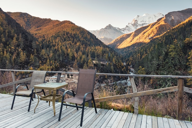 Chairs with table on wooden balcony with valley in autumn at evening