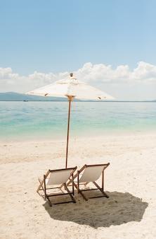 낙원의 황량한 해변에 의자 라운지.
