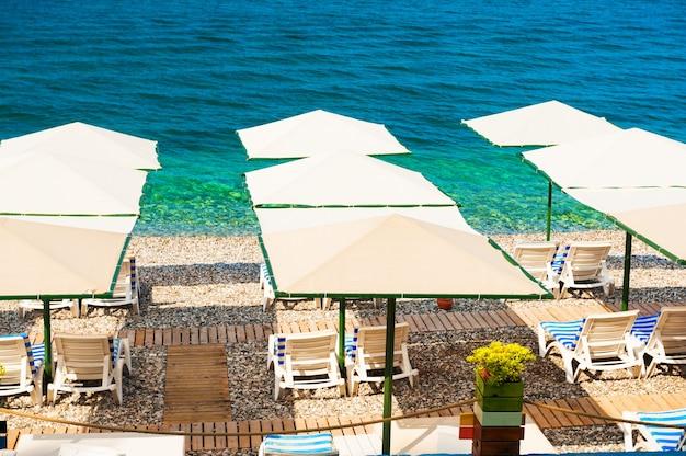 Шезлонги и зонтики на пляже в кемере, турция. путешествие и отдых