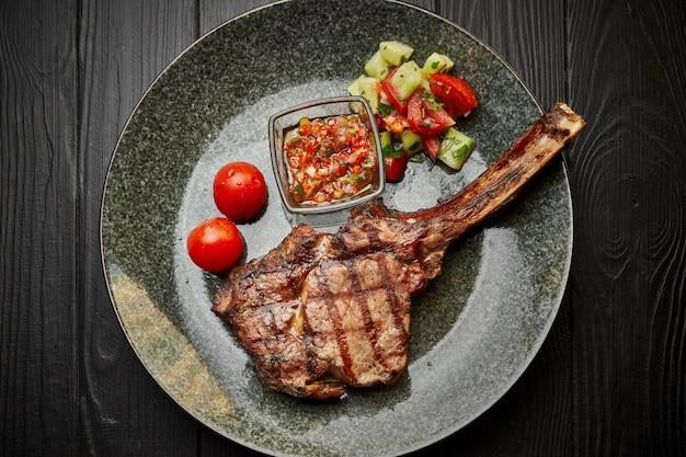 Мясо чалагач на тарелке с салатом, помидорами и соусом