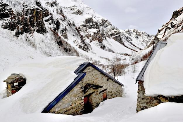 冬の高山の雪に埋もれた村のシャレー