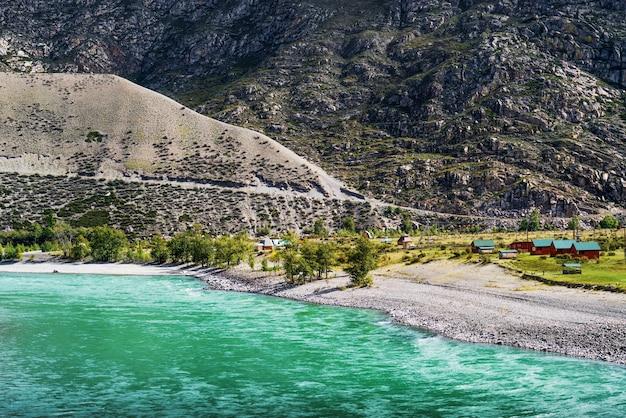 アルタイ山脈のカトゥニ川のほとりにある山川のエアタッシュキャンプの岸にあるシャレー