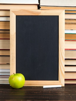 Chalk black board, apple and chalk, against books, copy space.