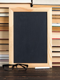 Chalk black board, glasses and chalk, against books, copy space.