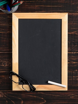 Chalk black board, glasses and chalk on a wooden table, copy space.