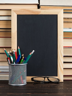 Chalk black board, glasses, stand with pens, pencils and chalk, against books, copy space.