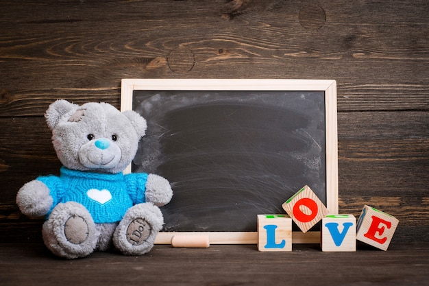 Доска мела и плюшевого медведя на деревянном фоне