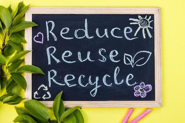 분필 보드 재사용 재사용 녹색 잎과 분필 조각이 있는 노란색 배경에 재활용 기호입니다. 평면도.