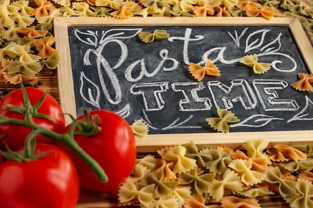 チョークボードは、生のファルファッレ、フレッシュトマト、黒胡椒を添えた木製の卓上でパスタタイムにサインします。
