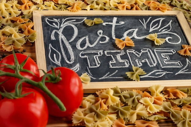 Chalk board sign pasta time on a wooden tabletop with raw farfalle, fresh tomatoes and black pepper.