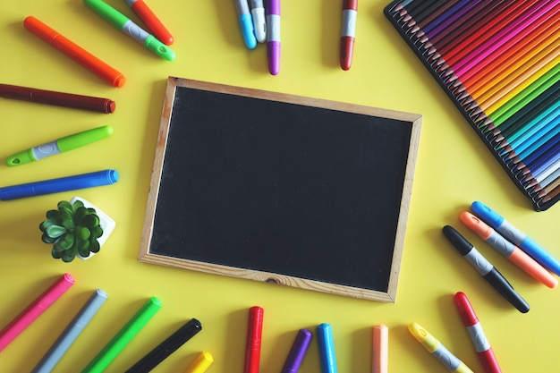 Chalk board with colored markers and pencils on yellow background. school supplies for kids. top view.