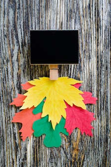 Chalk board with colorful paper leaves on vintage textured wooden table.