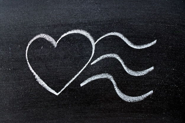 Chalk drawing as heart shape with waves on slate surface