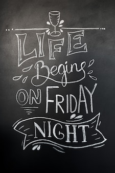 Chalk hand-drawn lettering. life begins on friday night lettering