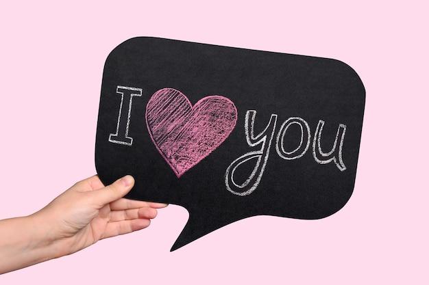 ピンクの背景に女性の手に「愛しています」と刻まれたチョークプレート。
