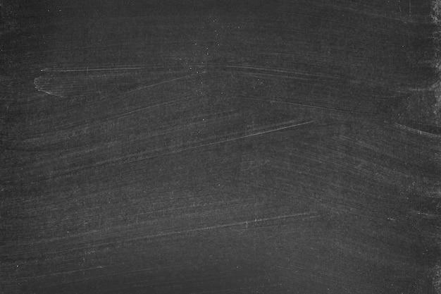 チョークを黒板にこすりつけた。抽象的な黒板の背景