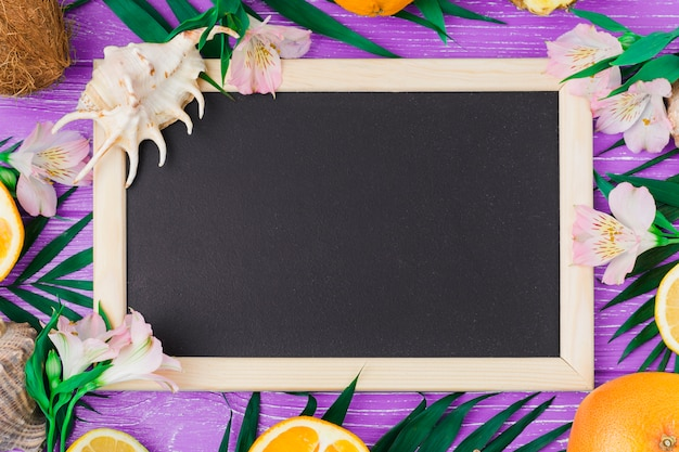 Chalkboard among plant leaves near flowers and fruits