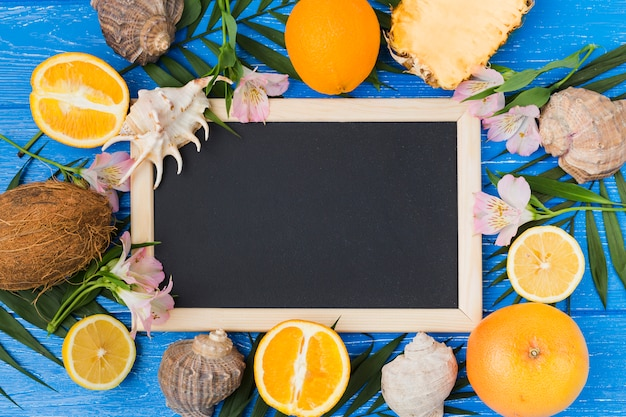 Chalkboard among plant leaves with fruits and flowers on desk