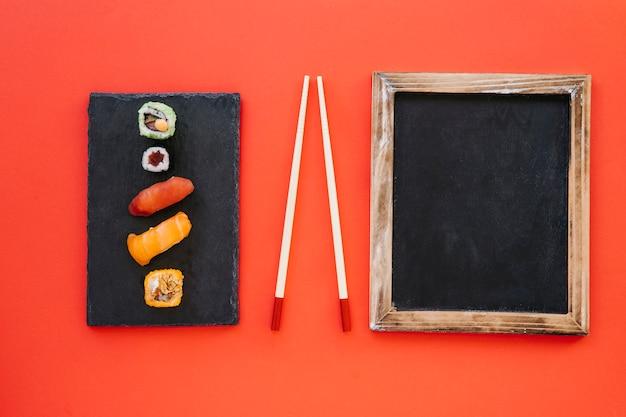 Доска и палочки для еды рядом с рулонами