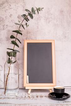 Chalkboard beside cup and branch in bottle