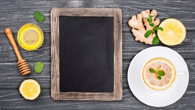 Chalkboard beside cup with lemon tea and honey
