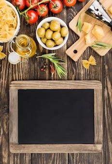 Доска рядом с фузилли с оливками и овощами