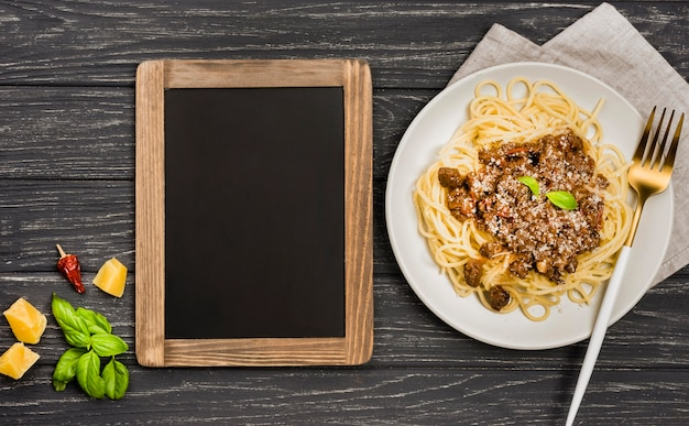Chalkboard beside plate with spaghetii bolognese
