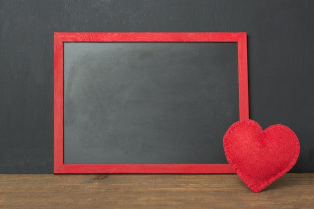 Chalkboard frame with place for your text and red felt heart as decor on wooden table. valentine's card. .
