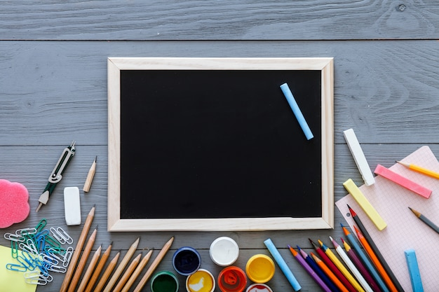 Chalkboard on grey dark desk with colorful pencils, paints, other school supplies for schoolwork, back to school sale concept, creative workplace for new learning year, top view, copy space