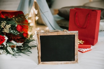 Chalkboard in front of bouquet and gifts
