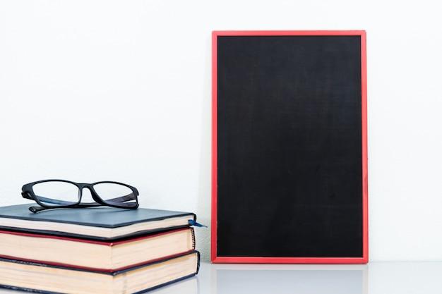 Chalkboard mock up frame and old books with eyeglasses