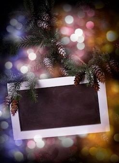 焦点がぼけたライトの上の松の枝の黒板