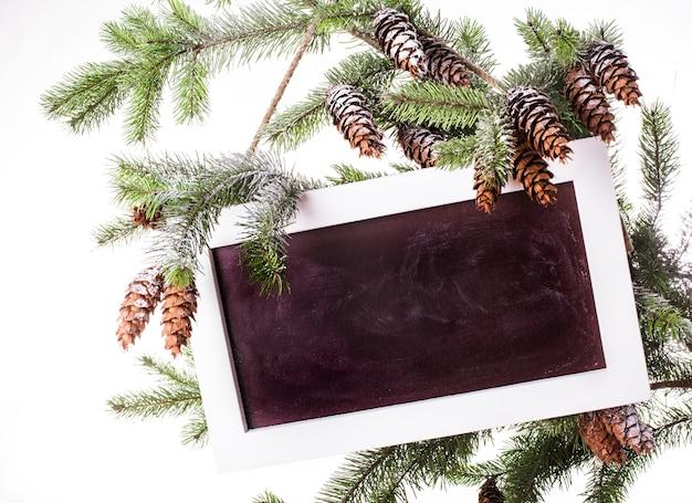雪の下の松の枝の黒板