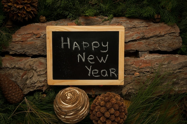 松と円錐形の枝と木製の背景に黒板新年おめでとうございます