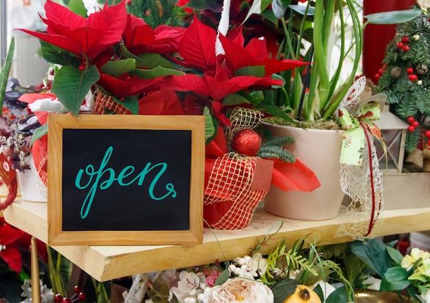 Классная доска открыта в цветочном магазине во время праздничного зимнего сезона