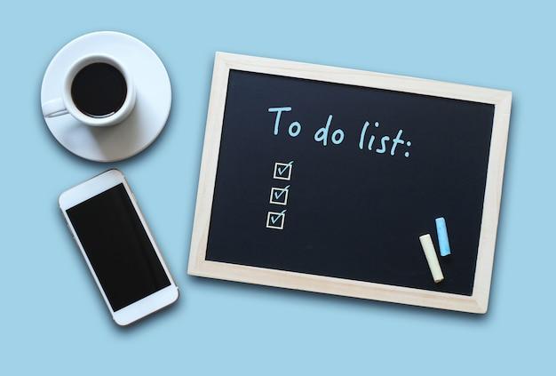커피와 휴대폰이 있는 빈 할 일 목록이 있는 칠판 또는 칠판 개념.