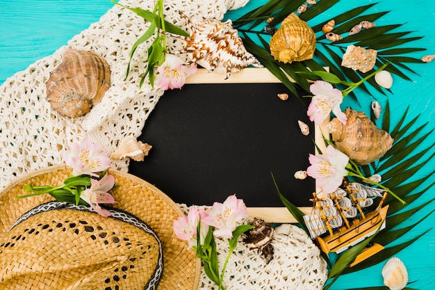 Chalkboard between plant leaves with flowers near seashells and hat