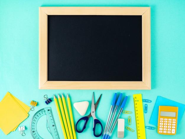 Chalkboard, school supplies on white table, blue wall.