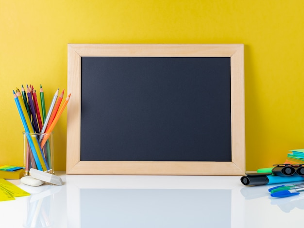 Chalkboard and school supplies on white table by the yellow wall. back to school concept