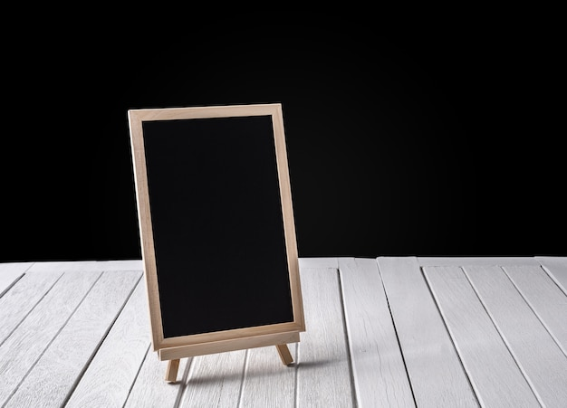 The chalkboard on the stand on wooden floor and black background