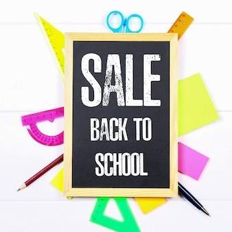 Chalkboard surrounded by stationery on a white wooden table. back to school sale.